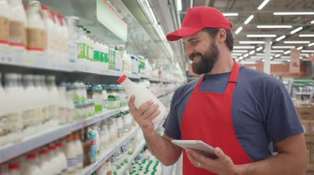 scaffale supermercato : Smiling supermarket employee checking the quality of the milk Filmati Stock