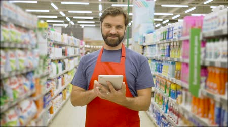 scaffale supermercato : Handsome smiling supermarket employee with beard using digital tablet standing among shelves In supermarket