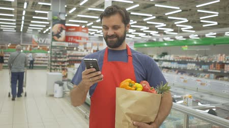 afdeling : Smiling supermarket employee using mobile phone and holding shopping bag in supermarket