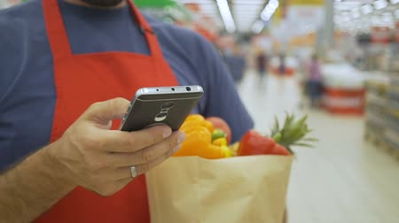 afdeling : supermarket employee using mobile phone and holding shopping bag in supermarket