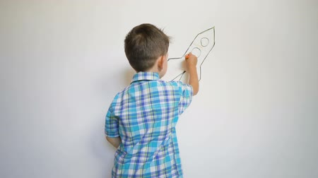 paletta : Cute little boy painting on white wall