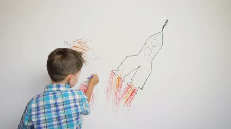 small pen : little child drawing thr rocket on white wall Stock Footage