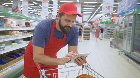 giderler : supermarket employee leaning on the shopping cart and using mobile apps on his tablet Stok Video