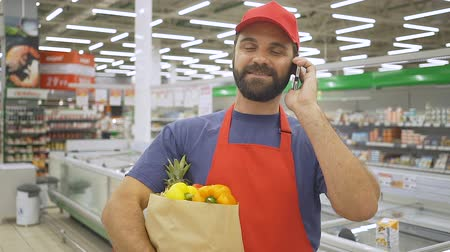 Handsome delivery man in red uniform talking to mobile and holding grocery paper bag with vegetables
