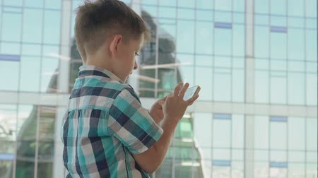 Little boy with mobile phone in the background with skyscrapers. Modern children in the megalopolis use a mobile concept. 動画素材