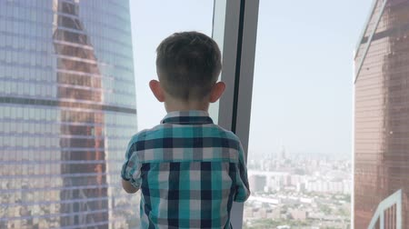pedleri : Child taking photo with his smartphone in the background with skyscrapers. Modern children in the megalopolis use a mobile concept.