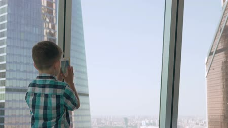Child taking photo with his smartphone in the background with skyscrapers. Modern children in the megalopolis use a mobile concept.