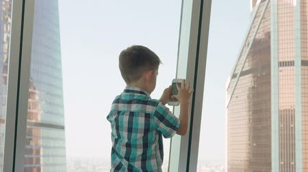 Little boy with mobile phone in the background with skyscrapers. Modern children in the megalopolis use a mobile concept. Stok Video