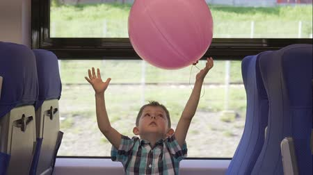 Cute little boy playing with pink balloon in the train, while it moving. Child going on vacations and traveling by railway.