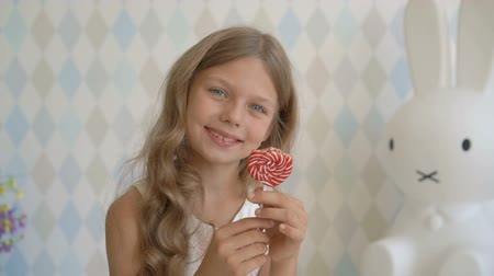 Beautiful little girl with lollipop, happy little girl eating candy at home