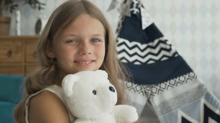 Cute girl is hugging a white teddy bear, looking at camera and smiling