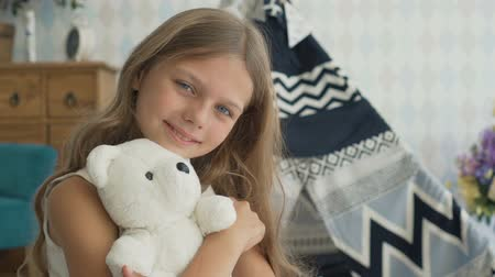 peluş : Cute little girl is hugging a teddy bear, looking at camera and smiling Stok Video