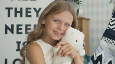 Sweet girl is hugging a teddy bear, looking at camera and smiling