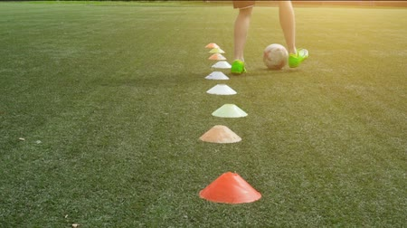 Soccer player running in football field leading ball between cones