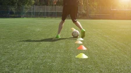 Leg skill training on football field. Soccer player running in football field leading ball between cones