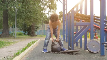 Little boy lifting heavy weight on the outdoor sports ground