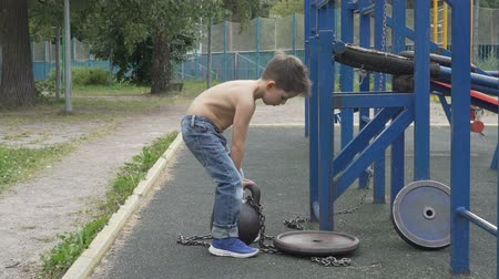 Little boy lifting heavy kettlebell on the outdoor sports ground Dostupné videozáznamy