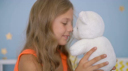 Cute girl hugging teddy bear while sitting on bed at home Dostupné videozáznamy
