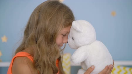 Cute girl hugging teddy bear while sitting on bed at home Stok Video
