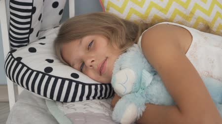 Cute little girl sleeping with teddy bear in bed Stok Video