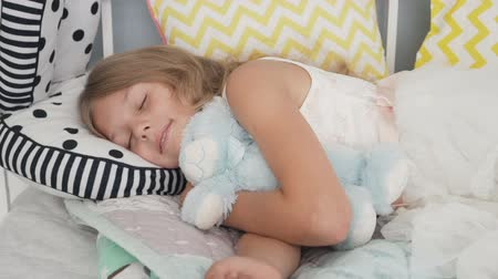 Cute little girl sleeping with teddy bear in bed at home