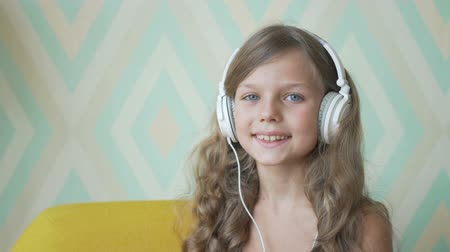 Cute little girl in headphones listening to music using a tablet, looking at camera and smiling at home