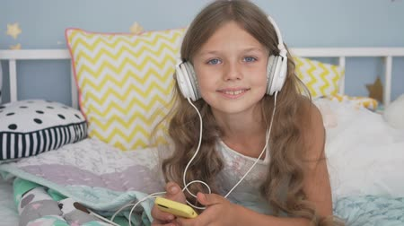 Happy smiling girl lying with smartphone and headphones in bed listening to music at home