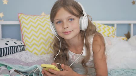 이어폰 : Happy smiling girl lying with smartphone and headphones in bed listening to music at home