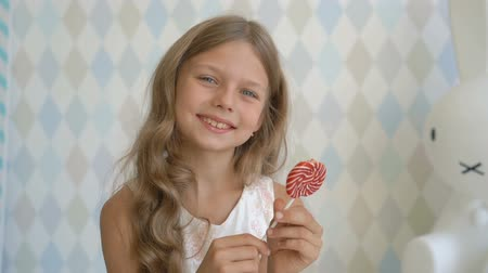 Funny child with candy lollipop, happy little girl eating lollipop, kid eat sweets at home