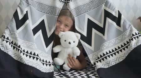 Lovely little girl embracing her toy bear and looking at camera while sitting on the floor in tent