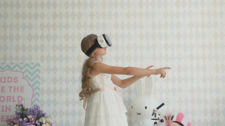 Happy amazed little girl wearing virtual reality goggles watching movies or playing video games.