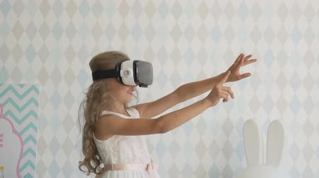 little girl wearing virtual reality goggles watching movies or playing video games.