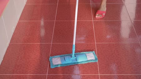 spilled : Woman cleaning red tile floor with blue microfiber mop Stock Footage