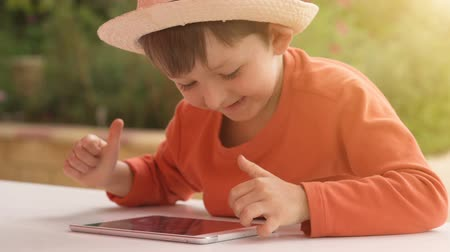 Little boy playing with tablet on summer nature background