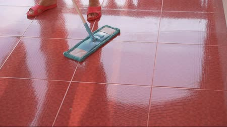 Girl cleaning red tile floor with blue microfiber mop