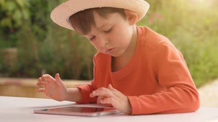 Child playing with digital tablet on summer nature background