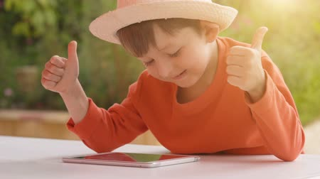 Boy child playing with tablet on summer nature background