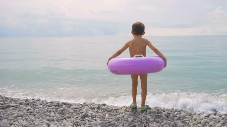 Little boy with inflatable ring ready to swim