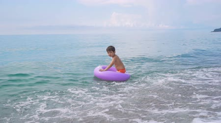 Child floating in sea on inflatable ring