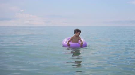 Cute little boy floating in sea on inflatable ring