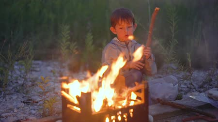 Little boy sitting by the fire Stok Video