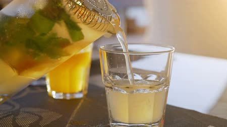 кувшин : Lemonade with orange, mint and ice pouring into glass