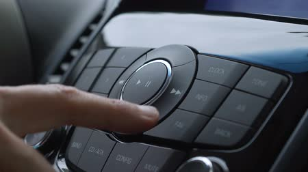 Male finger pressing radio button on car control panel