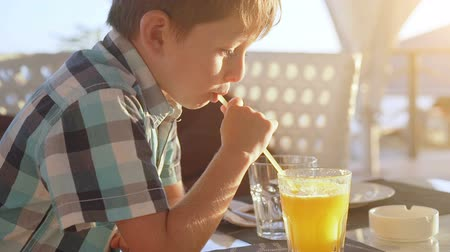 Cute little boy drinking fresh orange juice from glass in city cafe