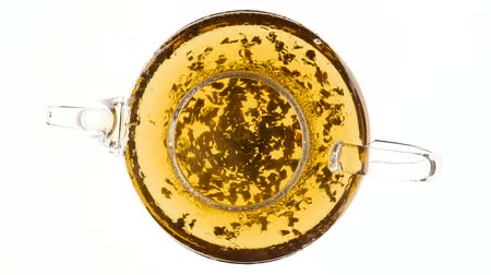 Brewing black tea in glass teapot. Top view on white background Stok Video