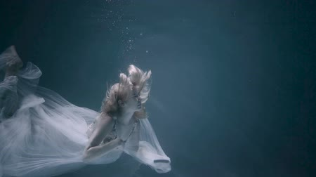 Young women in a white dress swimming under the water.