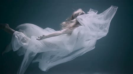 Young beautiful woman in white dress swimming underwater