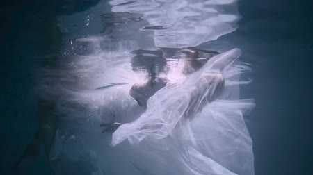 Beautiful woman swimming underwater in white elegant dress