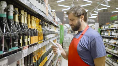 deterjan : supermarket employee in red aport scanning barcode at wine section in supermarket Stok Video