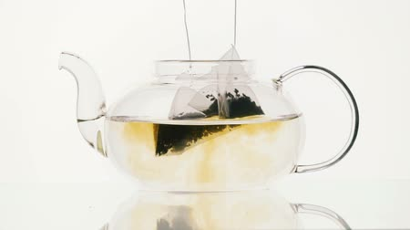 dois objetos : Teapot glass with two tea bags on a white background Stock Footage